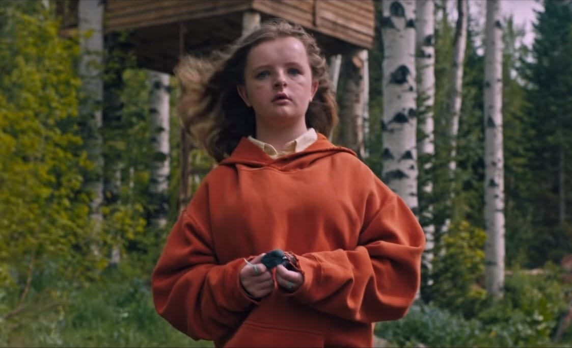 Charlie (Milly Shapiro), a white girl with long dirty blonde hair and blue eyes, standing in front of a tree house and a forest of birch trees. She is wearing an orange-ish red hoodie and is holding what appears to be a dead bird. She has two green strings tied around two different fingers.