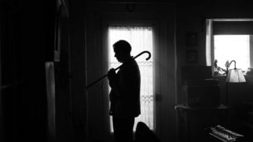 Mank standing in silhouette with a cane on his shoulder