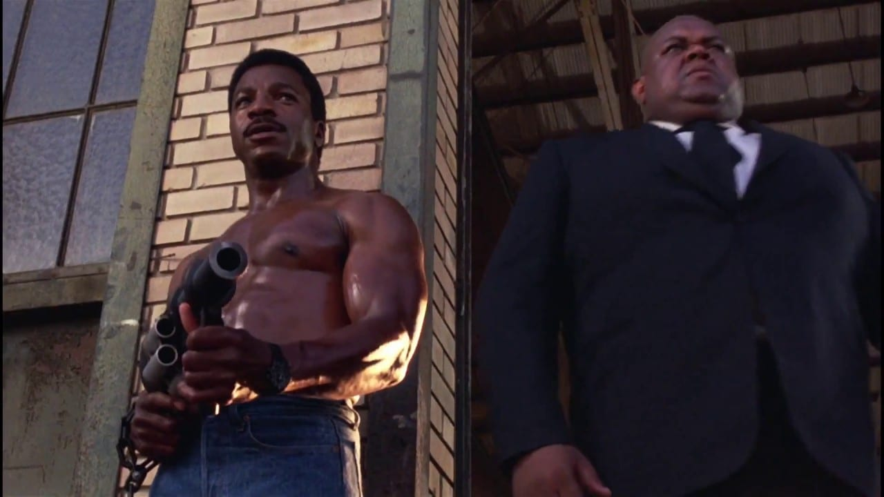 Action Jackson standing shirtless holding a weapon