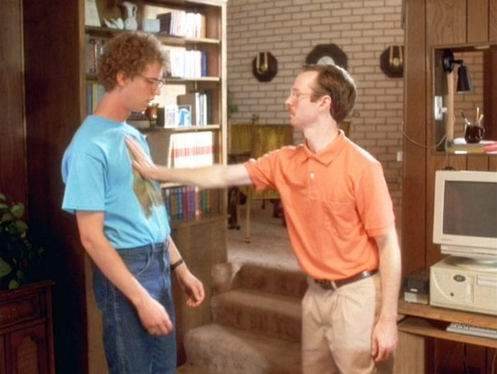 Kip (Aaron Ruell) shoving Napoleon (Jon Heder) at the bottom of their carpeted three-stair descent into their living room. Neither of them appear very emotive.