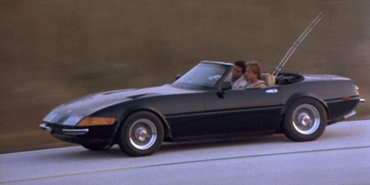 Crockett and Tubbs riding in black Ferrari, with fishing poles in the back of the car in TV show Miami Vice