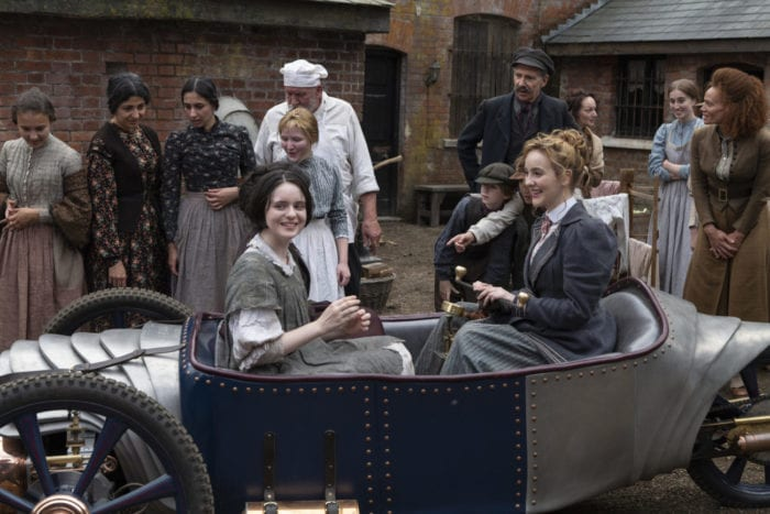 Penance and Myrtle sit in the small car surrounded by others looking on