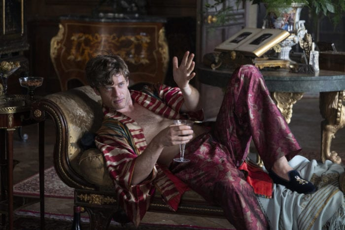 Hugo speaks and gestures from a couch while holding a glass of wine