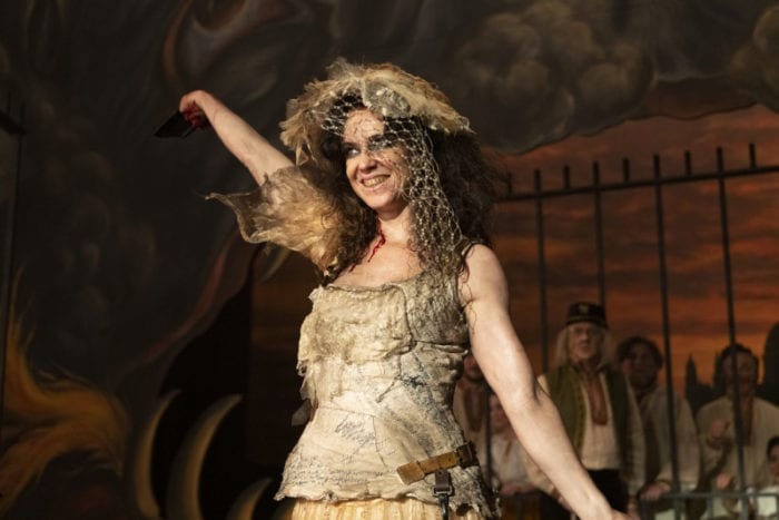 Maladie flourishes a hand into the air onstage at the opera house