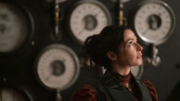 Amalia True stands in profile in front of a wall of clocks, looking upwards