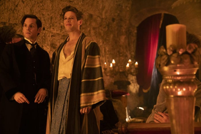 Hugo and Augustus stand next to each other at the Ferryman's party
