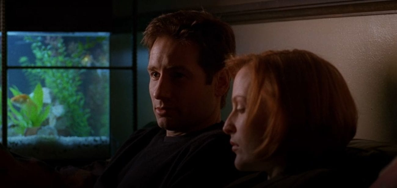 Mulder and Scully sit on a couch next to a fish tank