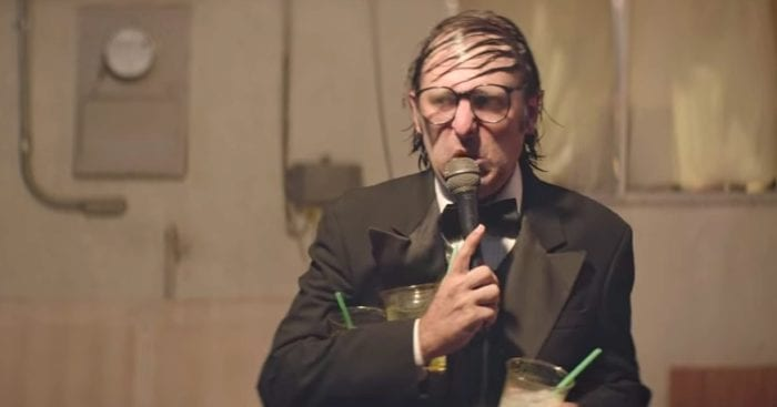 """Greg Turkington juggles three margaritas while performing comedy with an oily comb over in """"Entertainment"""" by Rick Alverson"""