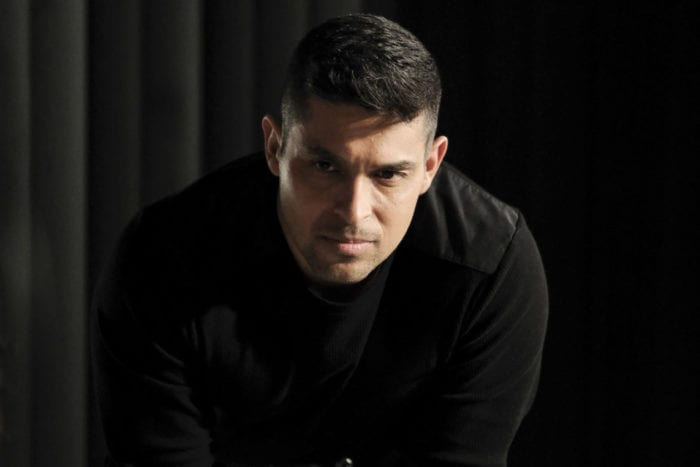 NCIS Agent Nick Torres (Wilmer Valderrama) leans seriously over a table