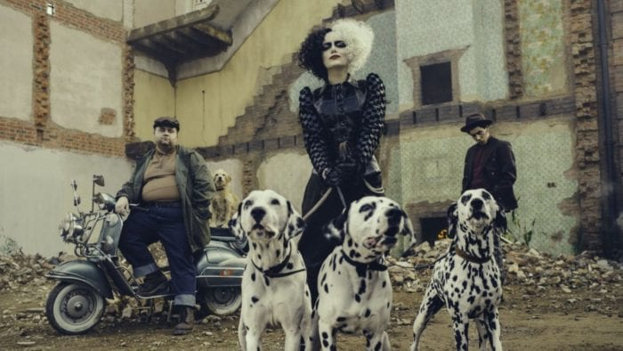 Cruella holds three leashed dalmatians in front of her sitting two friends.