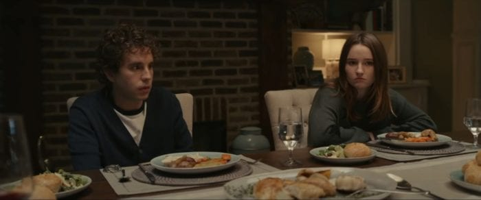 Evan and Zoe sit on the same side of a dinner table