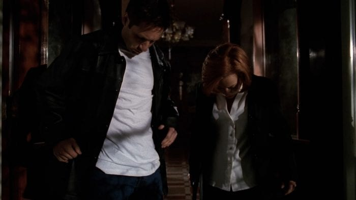 Mulder and Scully look down at their clothes in confusion as they leave the haunted house in The X-Files Season 6