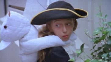 Still from Me the Terrible. The pirate girl looks mischievously over her shoulder with her teddy bear wrapped around her neck.
