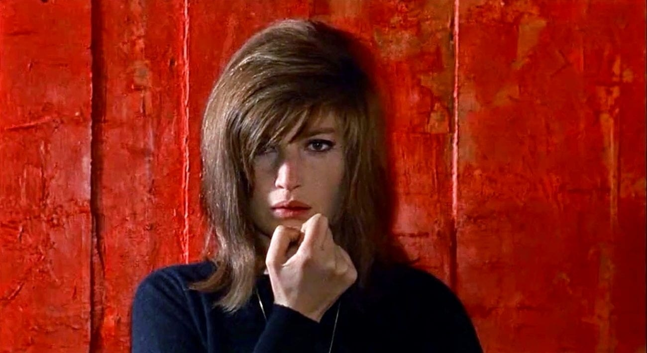 Monica Vitti with a hand to her face in front of a red background