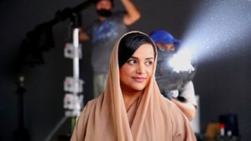 Nayla Al Khaja stands smiling while a film light shines behind her