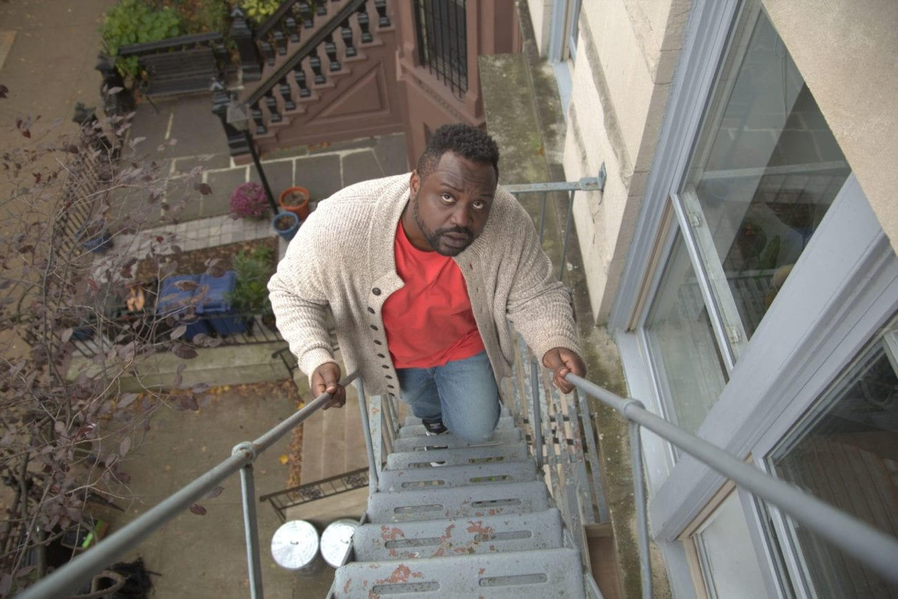 Charles looks up while walking up a fire escape.