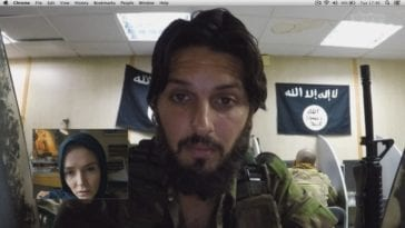 Bilel looks into the camera of the computer screen with Isis Flags hanging around them, Amy is shown in a smaller box on the computer screen