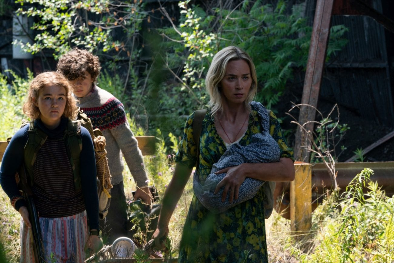 A mother carries her infant followed by her two teens in the woods.