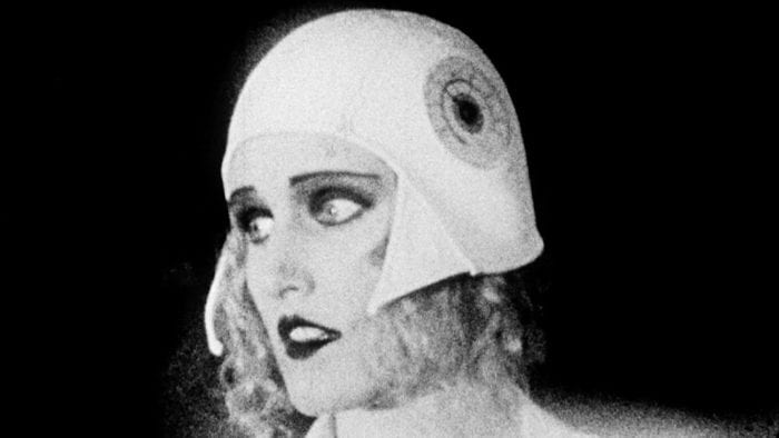 Still from Heart of the World. Anna, the state scientist, looks distressed. The shot is in black-and-white, and Anna is made up to look like a silent film actress.