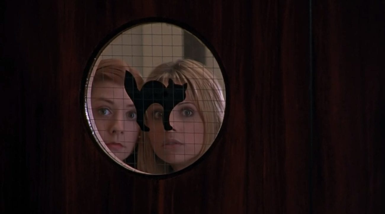 Willow and Buffy peering into a round window with a black cat on it