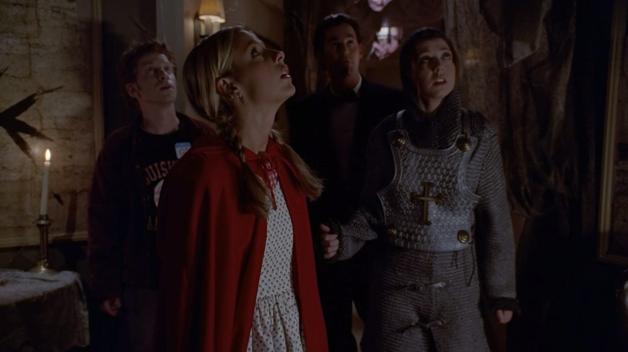 From left to right: Oz, Buffy, Xander, and Willow in their Halloween costumes looking up at the ceiling