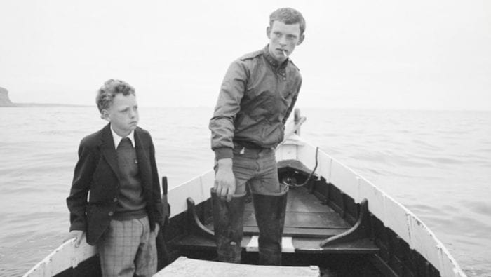 Still from Skinningrove depicting one of the photographs shown in the film. A young boy sits in a boat with an older boy. The young boy is wearing nice clothes and almost looks shell shocked. The older boy is smoking a cigarette.