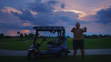 A shortless man stands next to a golf cart at dusk.
