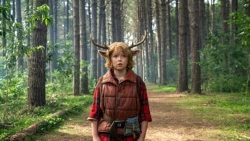 A boy with antlers stands on a trail in the middle of the forest.