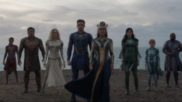 The Eternals stand in a V-formation on a cliffside with the ocean behind them