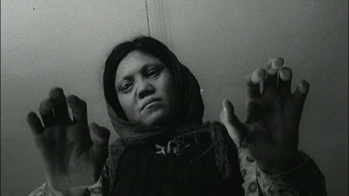 Still from The House is Black. A woman with leprosy looks at her hands on top of a glass table.