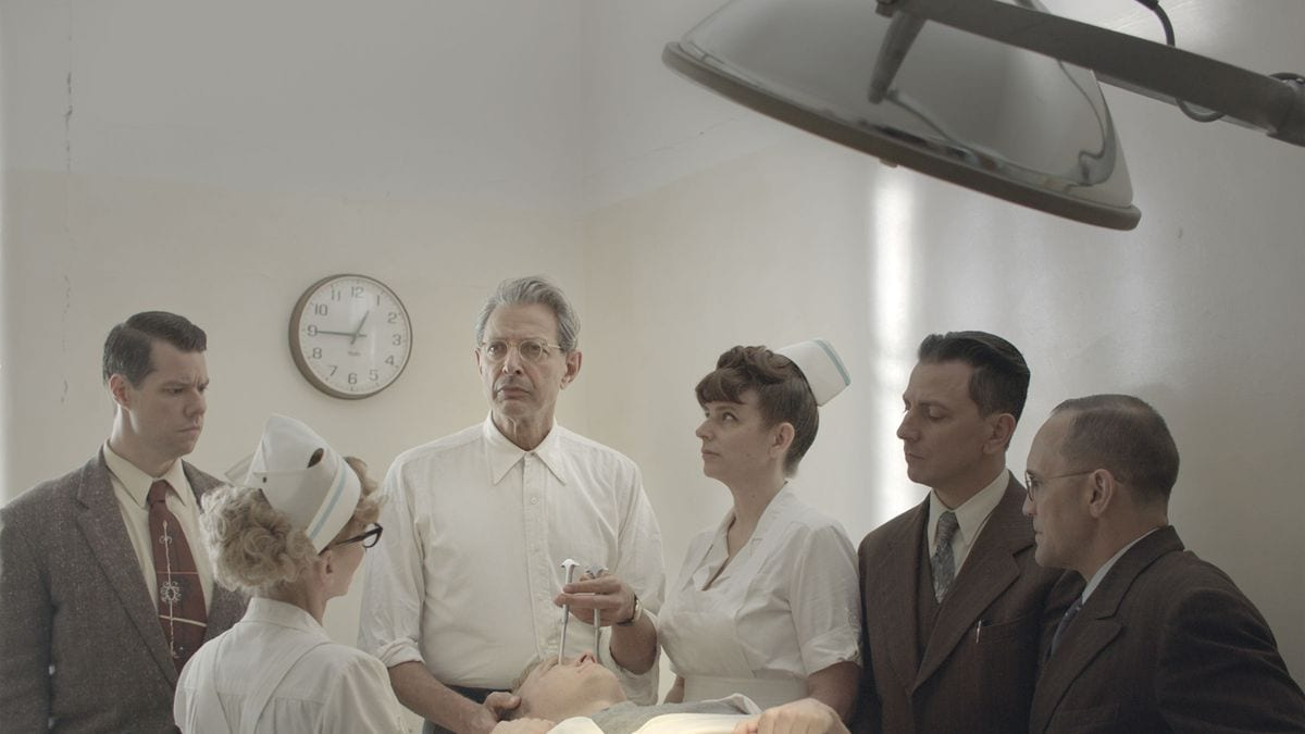 Goldblum's Dr. Wallace oversees a mental patient with his staff, seconds before a lobotomy procedure
