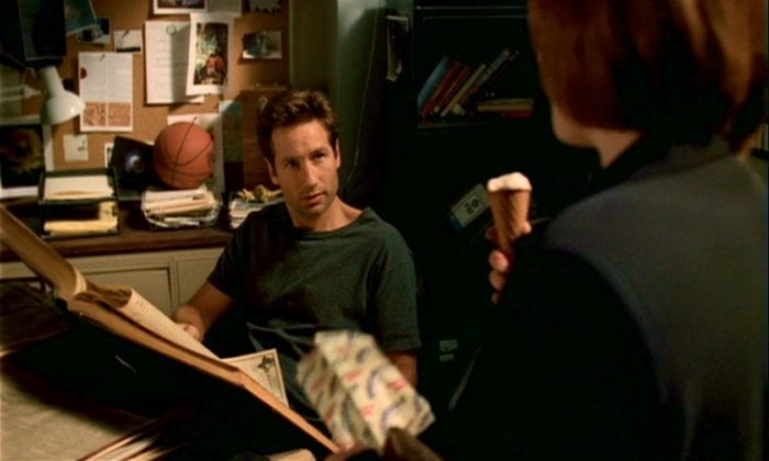 In the basement office, Mulder is reading old newspapers while Scully eats her tofutti dreamsicle