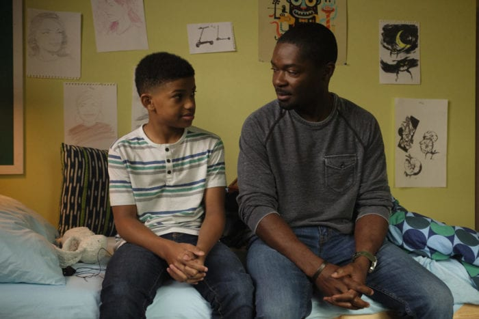 Amos and his son talk on a bed.