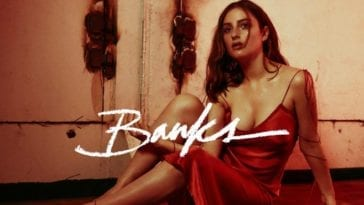 Banks in a slinky dress sitting with her knees up on the cover of iii