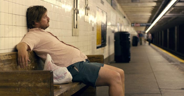 """In Rick Alverson's """"The Comedy,"""" Tim Heidecker, playing Swanson, lazily leans on a subway bench in New York City, his belly bulging out."""
