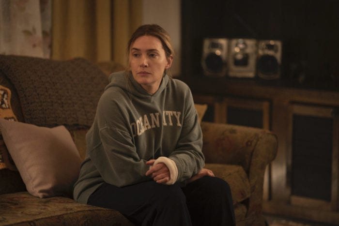 Mare (Kate Winslet) on her couch resting her newly casted arm.
