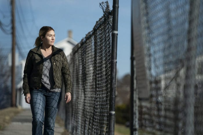 Mare (Kate Winslet) walks along a fence.