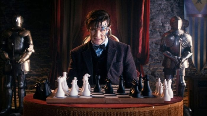 Matt Smith as Mr. Clever sits at a chessboard