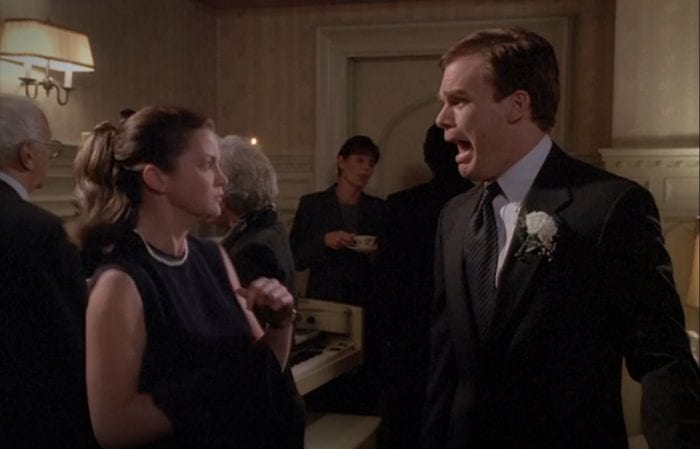 David screams at a women as they stand in the funeral home
