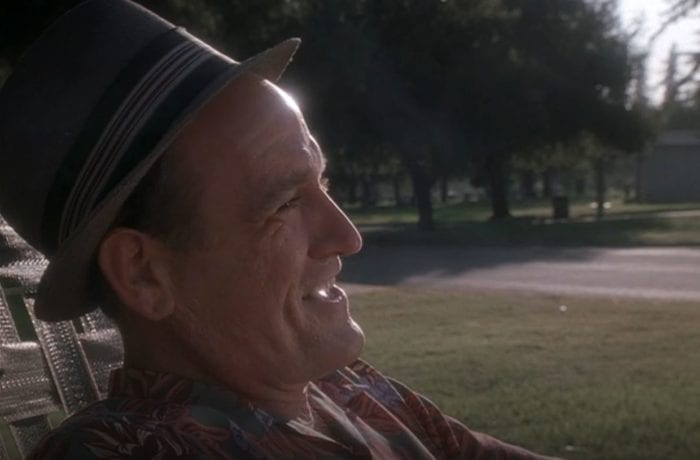 Nathaniel Fisher laughs in the sun while wearing a hat and sitting in a lawn chair