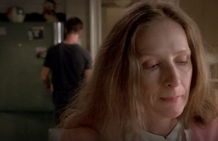 Ruth Fisher looks contemplative as Nate stands at the refrigerator in the background with his back to her, in the Six Feet Under pilot