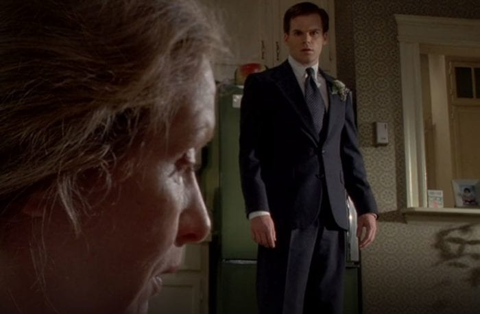 David in a suit and tie looks concerned as his mother Ruth, whose face is closer in the frame, to the left
