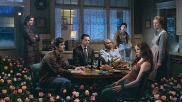 The cast of Six Feet Under sits and stands around a table with flowers in the foreground and a window behind them