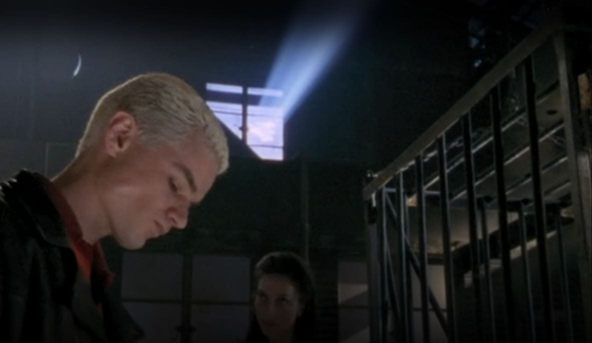 Spike looks downwards as Drusilla stands in the background and sun filters through a warehouse window