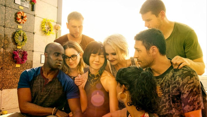 The main cast of Sense8 sit together, the sun shining behind them