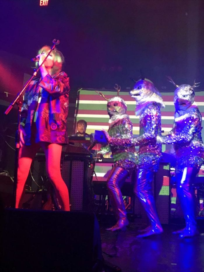 of Montreal's Kevin Barnes onstage with people in psychedelic costumes