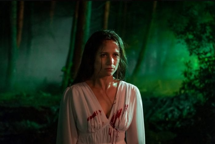 Enid stands in the woods where an eerie green light shines. her white dress has blood sprayed across the front of it.