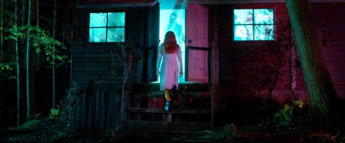 a woman in white walks into a cabin door where a beastly man is waiting on the other side of a brightly lit doorway