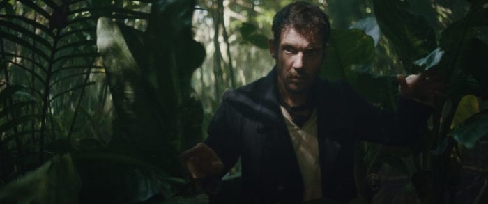 James steps through the shadows in the rainforest.