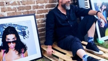 Gabriel Gornell sits outside next to a framed photo of Amy Winehouse